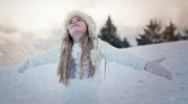 A young girl in winter clothing playing in the snow