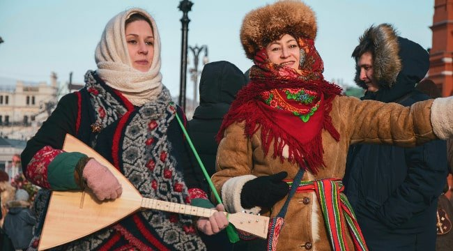 Russian women in traitional costumes invite to celebrating Maslenitsa
